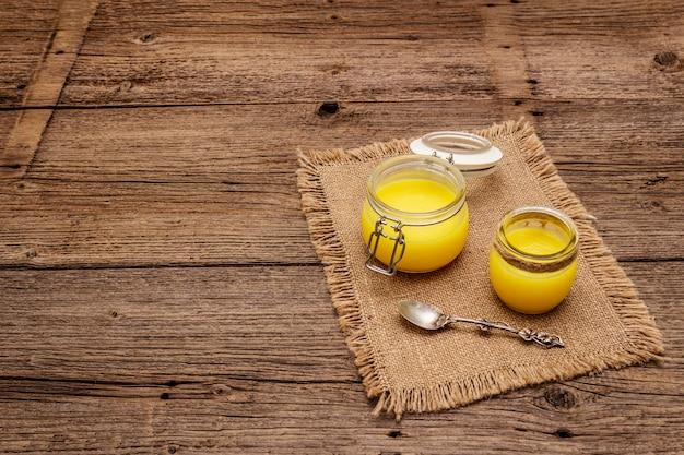 Ghi puro o desi (ghi), burro fuso chiarificato. concetto di dieta antiproiettile di grassi sani o piano stile paleo. vaso di vetro, cucchiaio d'argento su tela di sacco vintage.