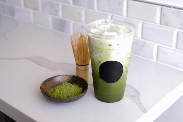 Ghiacci il tè verde del matcha nella tazza di plastica di portare via con l'adesivo posteriore rotondo.