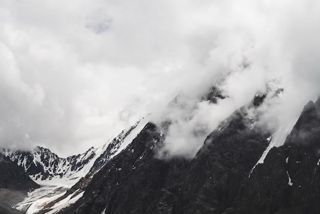 Ghiacciaio appeso e picco di montagna rocciosa innevato in nuvole basse.