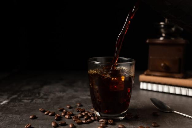 Ghiaccio caffè nero in un bicchiere sul tavolo di legno.