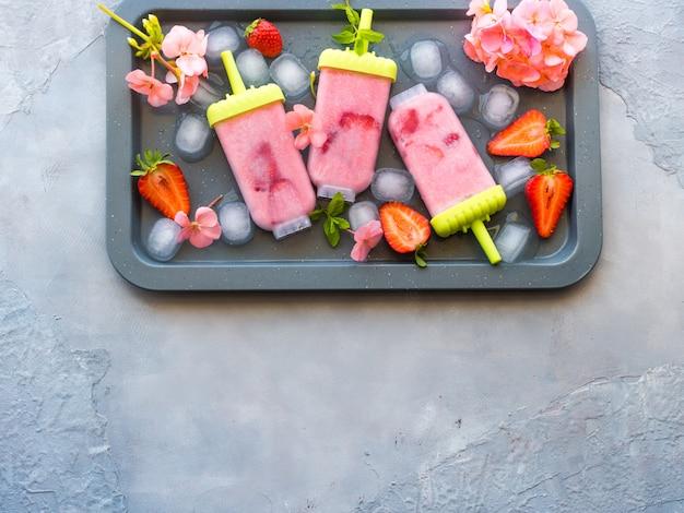 Ghiaccioli fatti in casa gelato alla fragola sul vassoio metall con cubetti di ghiaccio