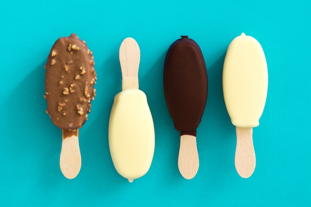 Ghiaccioli in bianco e nero del gelato al cioccolato isolati sulla vista superiore blu