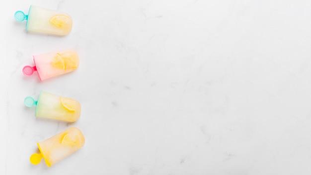 Ghiacciolo di ghiaccio congelato con agrumi su bastoncini colorati