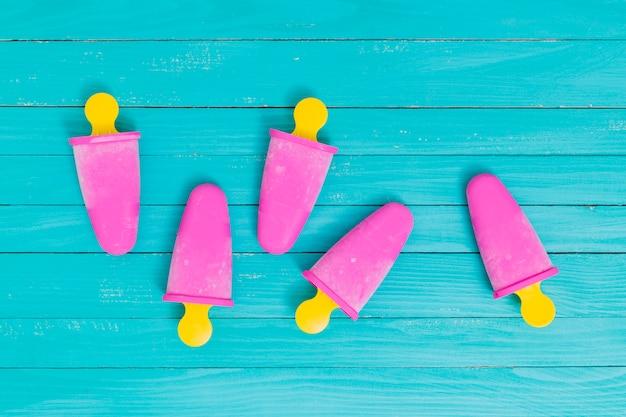 Ghiacciolo rosa su bastoncini gialli su superficie di legno