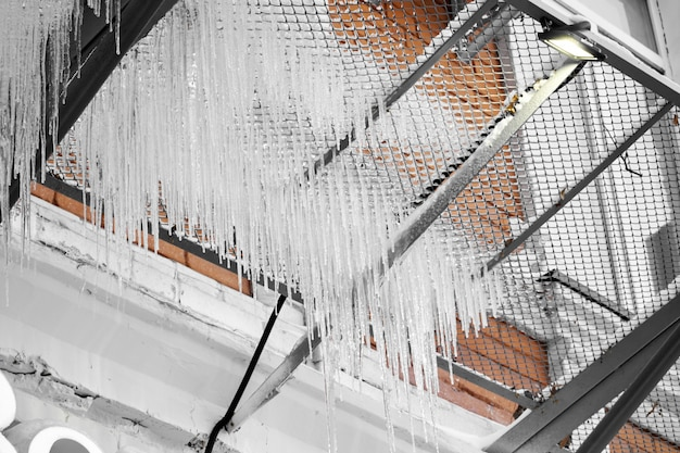 Ghiacciolo sul tetto del tubo, edificio coperto di ghiaccioli