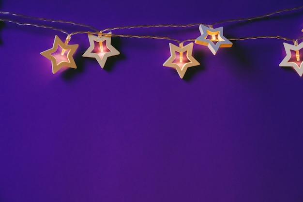 Ghirlanda a forma di stella illuminata sulla fine del fondo di colore su