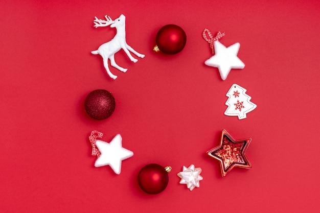 Ghirlanda con palline rosse, stelle bianche, albero di natale, cervi su carta rossa
