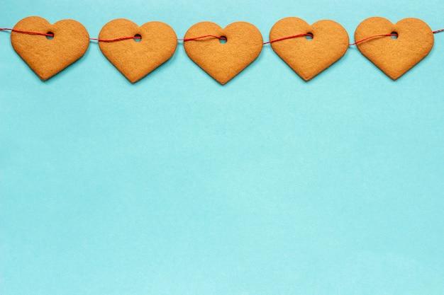Ghirlanda di biscotti allo zenzero a forma di cuori sul nastro rosso