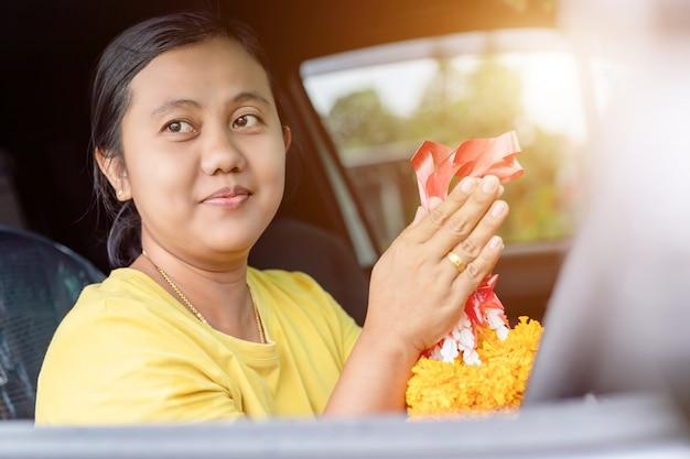 Ghirlanda di fiori donna in mano e pregando nella nuova auto per fortunati