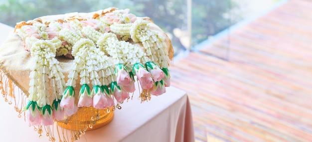Ghirlanda di fiori freschi nel vassoio di metallo su priorità bassa reception