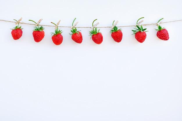 Ghirlanda di fragole mature rosse che appendono sulla molletta da bucato di legno sullo spago della corda su fondo di legno bianco