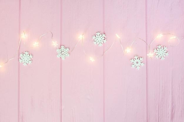 Ghirlanda di luci di natale con bordo di fiocchi di neve su legno rosa