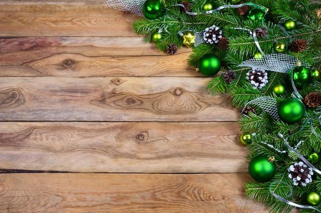 Ghirlanda di natale con palline verdi su sfondo di legno, copia spazio.
