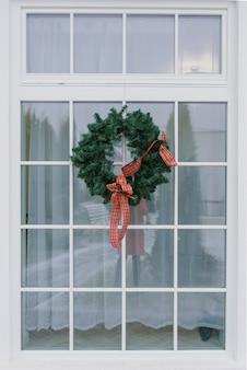 Ghirlanda di natale con un fiocco rosso su una finestra bianca in una casa privata