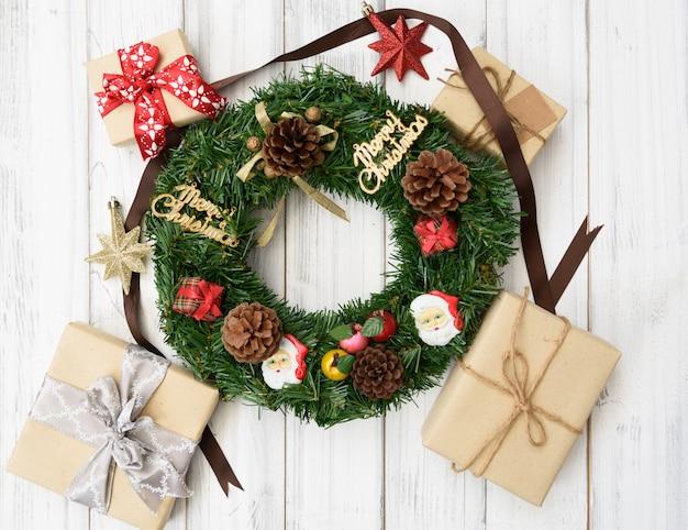 Ghirlanda di natale decorativa con scatole regalo, stella, pigne su fondo di legno bianco, piatto laici