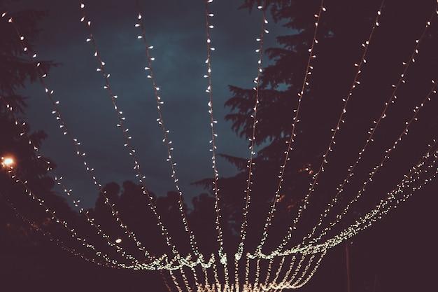 Ghirlanda di natale, incandescente con piccole luci sullo sfondo del cielo notturno