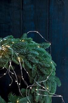 Ghirlanda di rami di albero di natale con un'aringa su uno sfondo scuro