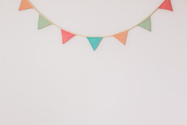 Ghirlanda di simpatiche bandiere da festa appese al muro. sfondo con copyspace che simboleggia la celebrazione della casa, il compleanno o l'umore festivo