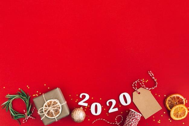 Ghirlanda fatta a mano di natale fatta di 2020 numeri in legno e rami di abete e altre decorazioni natalizie su sfondo rosso. natale, capodanno, concetto zero rifiuti.