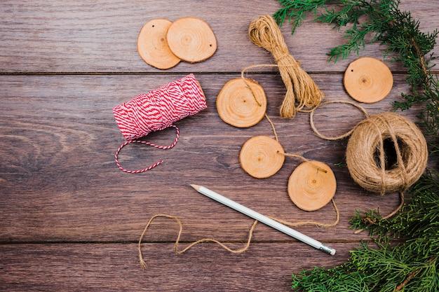 Ghirlanda fatta a mano per filo; fetta di ceppo d'albero in legno; matita e ramo di abete rosso sullo scrittorio di legno