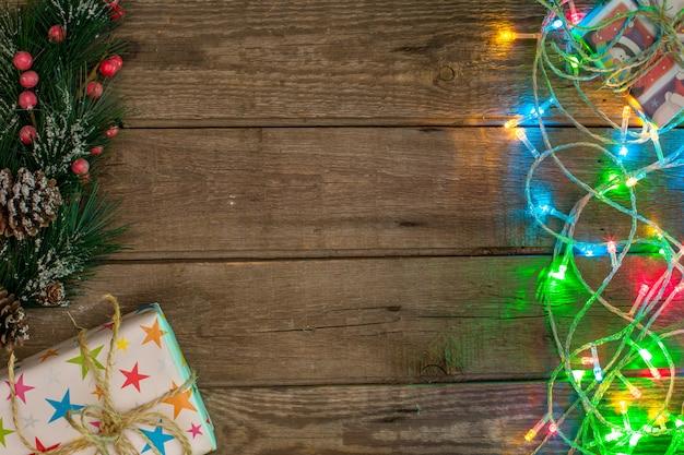 Ghirlande leggere colorate, regali e rami di pino sul tavolo di legno