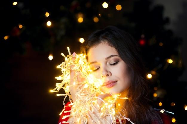 Ghirlande sorridenti e di conversazione della bella giovane donna delle luci a casa