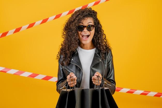 Giacca d'uso della giovane donna di colore d'avanguardia con i sacchetti della spesa di carta isolati sopra giallo con nastro adesivo