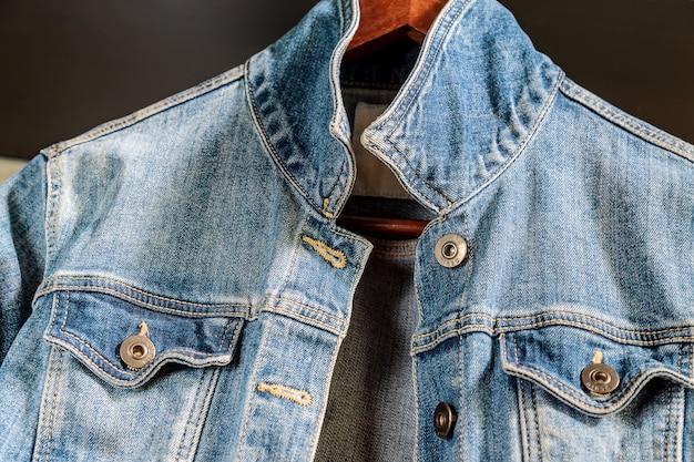 Giacca da donna in denim blu su appendiabiti in legno. vestiti alla moda.