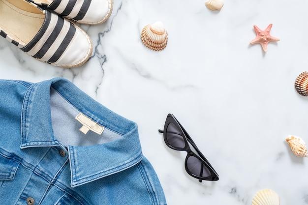 Giacca di jeans, occhiali da sole, sandali rigati, conchiglie, stelle marine su fondo di marmo.