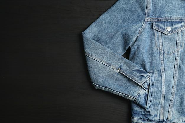 Giacca di jeans su sfondo nero, spazio per il testo