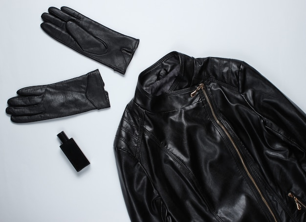 Giacca di pelle, guanti su superficie grigia.