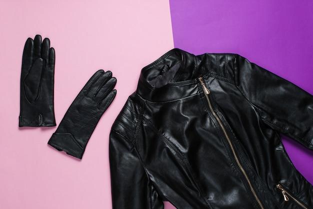 Giacca di pelle, guanti sulla superficie rosa.