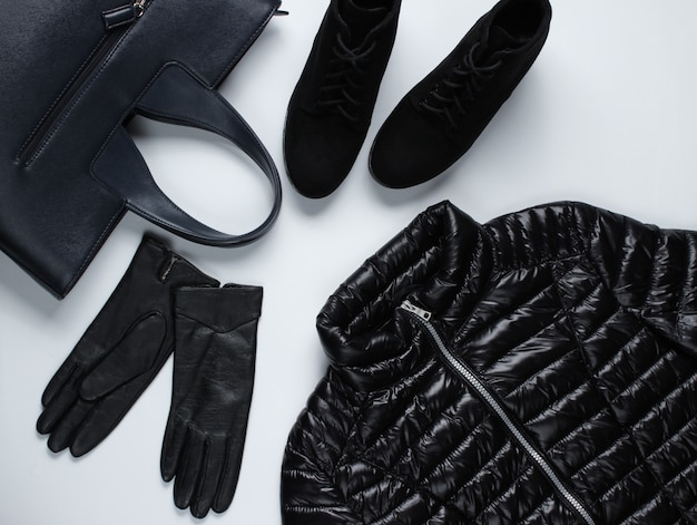 Giacca, guanti, borsa, stivali su una superficie grigia.
