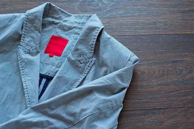 Giacca leggera in cotone a righe con una spilla alla moda su fondo di legno