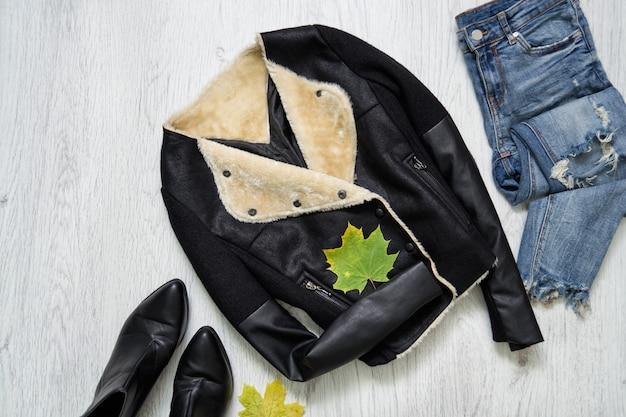 Giacca nera, stivali, jeans e foglie di acero