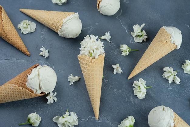 Giacinto bianco e gelato alla vaniglia nei coni della cialda su fondo blu. concetto di modello