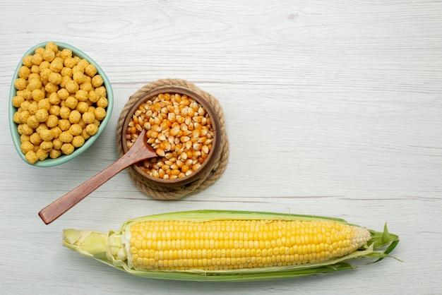 Giallo dei semi del cereale di vista superiore colorato con i cereali dentro il piatto su bianco