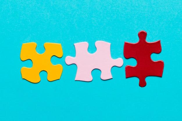 Giallo; pezzo di puzzle rosa e rosso su sfondo blu con texture