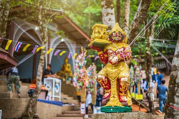 Giant guardian statue sulla via verso la pietra con l'impronta del signore buddha