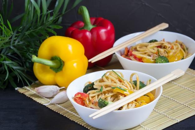 Giapponese due ciotole di soffriggere noodles con verdure, salsa di soia e peperoni su una stuoia di bambù