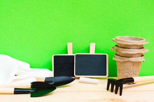 Giardinaggio domestico. strumenti di giardinaggio in miniatura, insegne di piante, vasi di carta per piantine e guanti sulla tavola di legno
