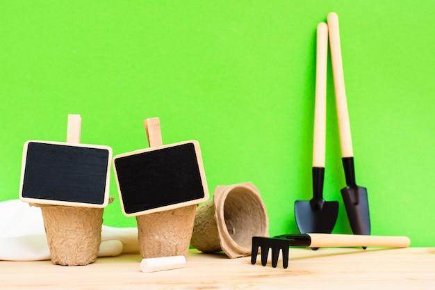 Giardinaggio domestico. tavole per iscrivere piante su vasi di carta per piantare, attrezzi da giardinaggio in miniatura e guanti sul tavolo di legno