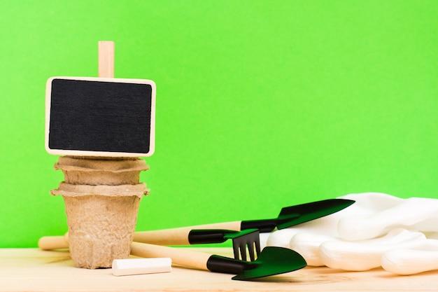 Giardinaggio domestico. un piatto per iscrivere piante su una pila di vasi di carta per piantare, attrezzi da giardinaggio in miniatura e guanti sul tavolo di legno