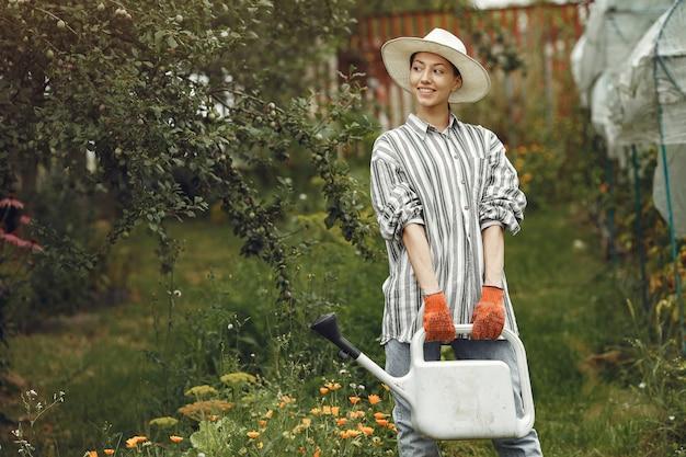 Giardinaggio in estate. donna che innaffia i fiori con un annaffiatoio. ragazza che indossa un cappello.