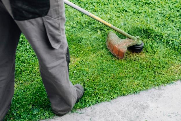 Giardiniere che falcia l'erba