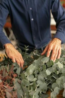 Giardiniere che organizza alta vista delle piante
