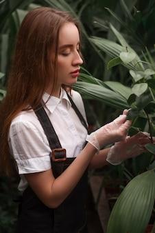 Giardiniere femminile lavora nel giardino botanico.
