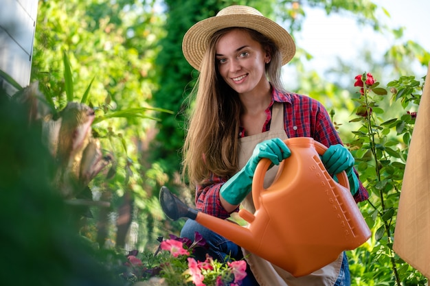 Giardiniere in cappello e grembiule con annaffiatoio per innaffiare i fiori nel giardino di casa. giardinaggio e floricoltura