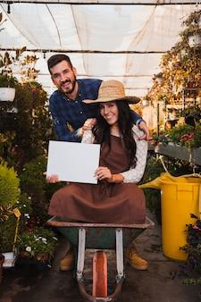 Giardinieri con la carriola che mostra il foglio di carta