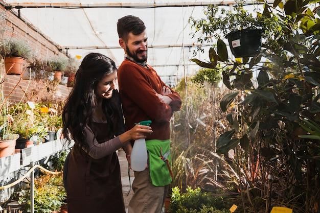 Giardinieri sorridenti che spruzzano piante